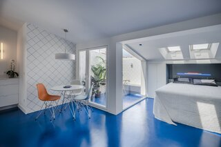 A Cramped Attic Apartment in Madrid Is Revived With Mirrored Walls and a Blue Floor